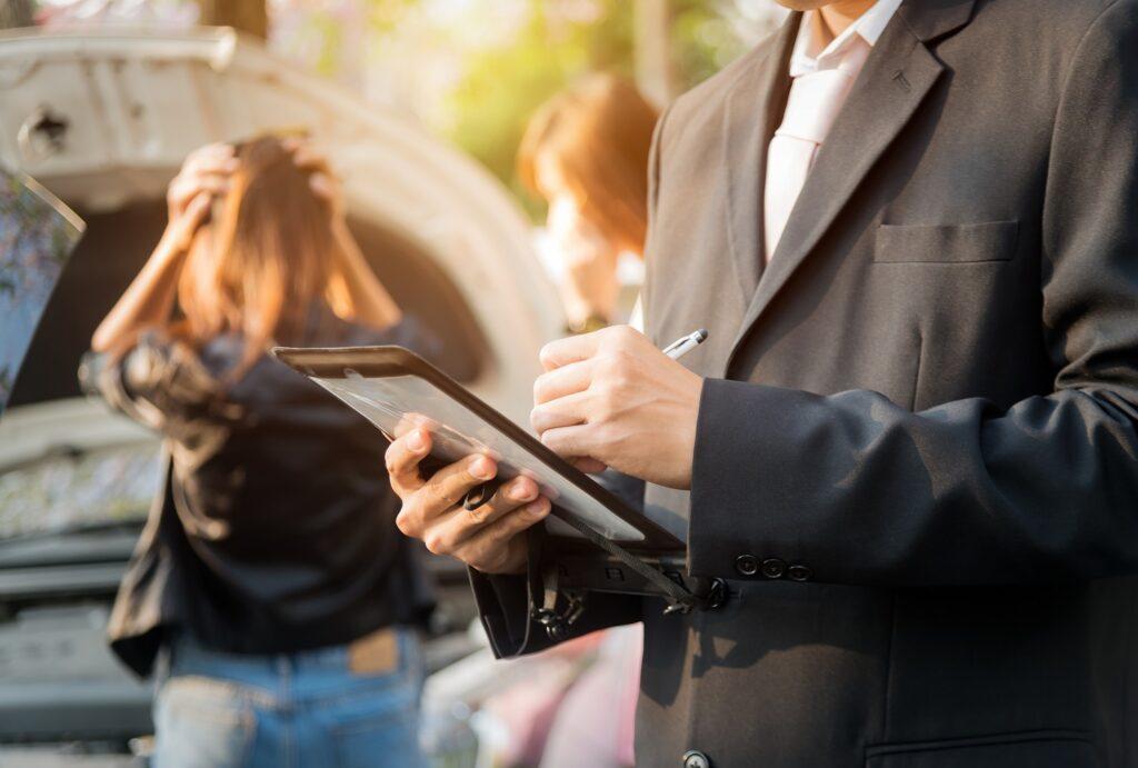 Verzekeraar die met een tablet de schade opneemt van een auto die na een verkeersongeval in de prak is gereden