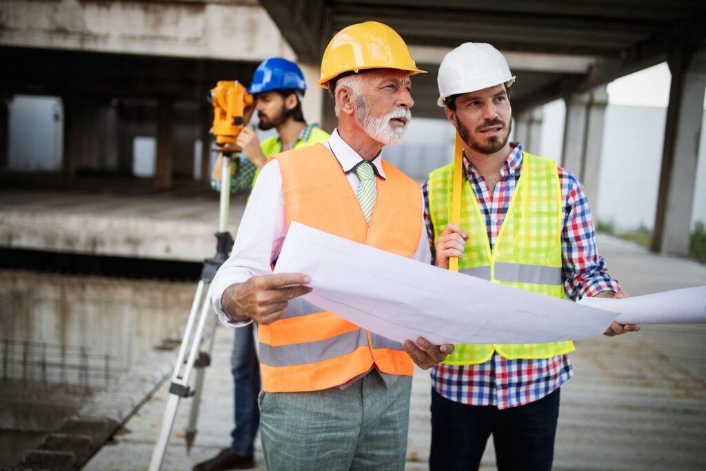 mannen die op de bouwplaats de bouwtekeningen nagaan