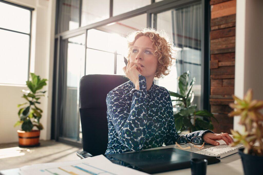 een vrouw zit van achter haar bureau na te denken over aansprakelijkheid